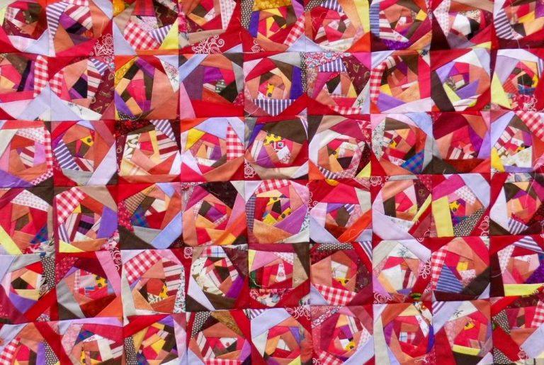 """Edel Lösch """"Rotes Crazy"""", Patchworkquilt (handgestickt auf den Nähten), Baumwolle, 150 x 115 cm, Rückseite: rot, Baumwolle, Einfassung: Druckstoff, rot, handgesäumt"""